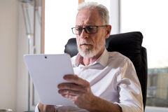 Senior businessman using a digital tablet, hard light. Senior businessman using a digital tablet in office, hard light Stock Photography