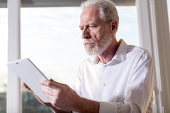 Senior businessman using a digital tablet, hard light. Senior businessman using a digital tablet in office, hard light Stock Image