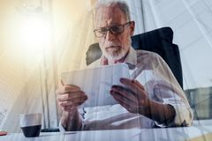 Senior businessman using a digital tablet, light effect, double exposure. Senior businessman using a digital tablet in office, light effect, double exposure Royalty Free Stock Images
