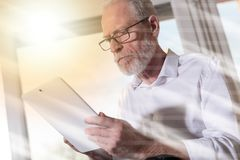 Senior businessman using a digital tablet, light effect. Senior businessman using a digital tablet in office, light effect Royalty Free Stock Image