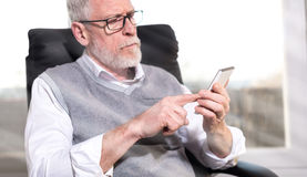 Senior businessman using his mobile phone, light effect Royalty Free Stock Photography