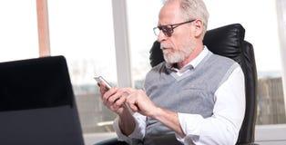 Senior businessman using his mobile phone Stock Image