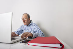 Senior businessman using laptop with book binder and cell phone on office desk Stock Images