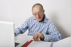 Senior businessman using laptop while reading file at office desk Royalty Free Stock Images