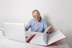 Senior businessman using laptop while reading file at office desk Stock Photos