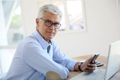 Senior businessman using smartphone and laptop Stock Photo
