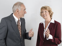 Senior businessman and woman in discussion. Mature businesswoman in conversation or negotiation with senior executive. Gray background stock image