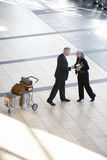 Senior businessman and woman shaking hands near luggage trolley in airport, side view, elevated view Royalty Free Stock Photography