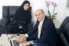 Senior Businessman working with Arabian Businesswoman wearing hijab Stock Image