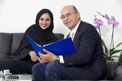 Senior Businessman working with Arabian Businesswoman wearing hijab Stock Photos