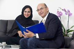 Senior Businessman working with Arabian Businesswoman wearing hijab Stock Photos