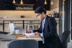 Senior Businessman working at coffee shop. Asian senior Businessman read meeting note on book at coffee shop while drinking hot coffee in cafe. working out of Royalty Free Stock Photos