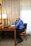 Senior Businessman Working in Hotel Room Stock Images
