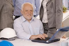 Senior businessman working on laptop. Portrait of senior businessman working on laptop computer, looking at camera, smiling, coworkers standing behind Royalty Free Stock Photography
