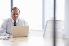 Senior Businessman Working On Laptop At Boardroom Table Stock Images