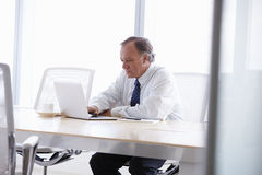 Senior Businessman Working On Laptop At Boardroom Table Royalty Free Stock Image