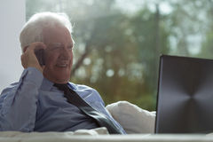 Senior businessman working on a laptop Stock Photo