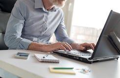 Senior businessman working on laptop, hard light Stock Images