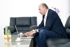 Senior Businessman working on laptop in his office Royalty Free Stock Photos