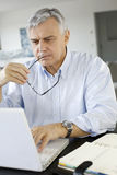 Senior businessman working on laptop at home Stock Photos