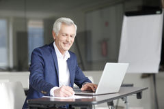 Senior businessman working on laptop Royalty Free Stock Images