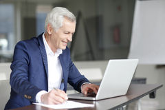 Senior businessman working on laptop Royalty Free Stock Photo