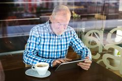 Senior businessman working on tablet in cafe Stock Photos