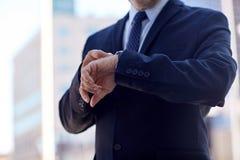 Senior businessman with wristwatch on city street Royalty Free Stock Image