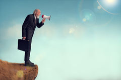Senior businessman yelling through a loudhailer. From a cliff edge Royalty Free Stock Images