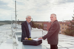Senior businessmen making a business deal on the roof of a build Royalty Free Stock Photo