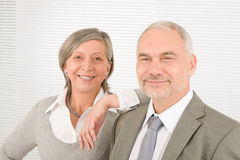Senior businesspeople lean over shoulder colleague Royalty Free Stock Images