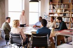 Senior Businesswoman Addressing Team Meeting Around Table Royalty Free Stock Photo