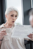 Senior businesswoman with coffee reading newspaper at office Stock Image