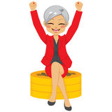 Senior Businesswoman Coins. Senior businesswoman with arms up celebrating her success sit on golden coins Royalty Free Stock Photo
