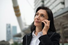Senior businesswoman discuss project by smartphone. Beautiful smile American senior businesswoman, 40 to 50 years old, hold smartphone to discuss Startup Stock Photos