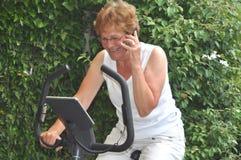 Senior businesswoman doing a workout. Senior businesswoman doing he workout and keeping in touch Stock Image