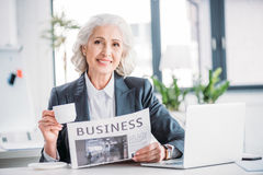 Senior businesswoman drinking coffee and reading newspaper at workplace Royalty Free Stock Images
