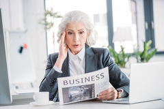 Senior businesswoman in formal wear reading newspaper at workplace Stock Photography