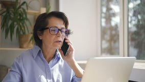 Senior businesswoman in glasses and blue shirt stock video