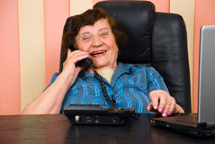 Senior businesswoman having funny conversation. Senior business woman having a funny conversation by telephone and she laughing,check also Business people Stock Photography