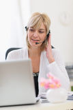 Senior businesswoman with headset sitting at table Stock Photography