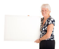 Senior Businesswoman Holding a Blank Sign. A senior businesswoman is holding a blank white sign Stock Images