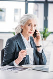 Senior businesswoman holding coffee cup and talking on smartphone. Serious senior businesswoman holding coffee cup and talking on smartphone Royalty Free Stock Photos