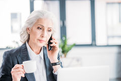 Senior businesswoman holding coffee cup and talking on smartphone. Serious senior businesswoman holding coffee cup and talking on smartphone Stock Photography