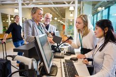 Businesswoman Holding Passport While Staff Working At Airport. Senior businesswoman holding passport while female staff working at airport check-in Royalty Free Stock Image