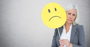 Senior businesswoman holding smiley face against grey background royalty free stock image