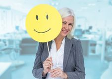 Senior businesswoman holding smiley face against wooden background royalty free stock images
