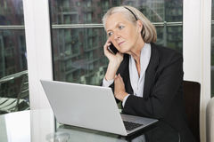 Senior businesswoman with laptop using cell phone while sitting at table Royalty Free Stock Image