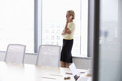 Senior Businesswoman On Mobile Phone In Boardroom Stock Photography