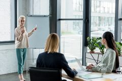 Senior businesswoman presenting project to colleagues at meeting. In office royalty free stock photography
